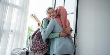 Asian hijab young women are happy to meet their mother when they open the door when they return home