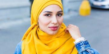 Beautiful Arabic muslim woman wearing yellow hijab, stylish female face portrait over city street