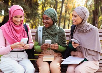 Three Modern Muslim Students Women Using Smartphones Sitting On Bench In Park Outdoors. Arabic Ladies In Hijab Texting On Phone Networking In Social Media. Educational Application, Gadget Lifestyle