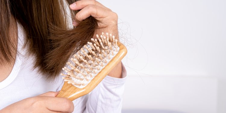 Closeup hand holding comb and hair fall problem.