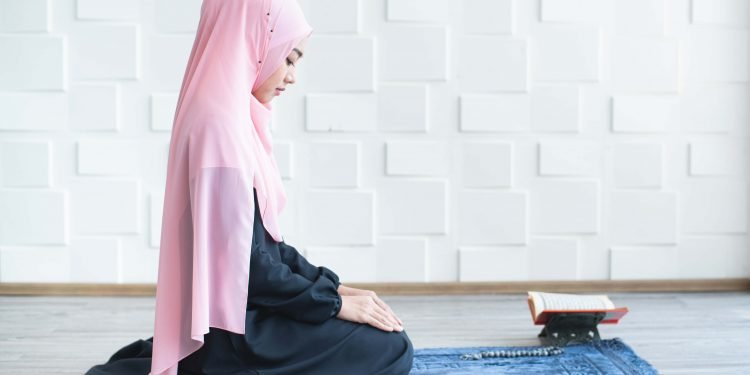 side view of asian beautiful young muslim student woman prayer in hijab praying on carpet mat indoors